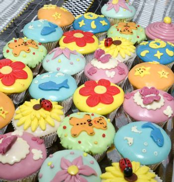 colorful cupcakes with various decorations, shallow dof