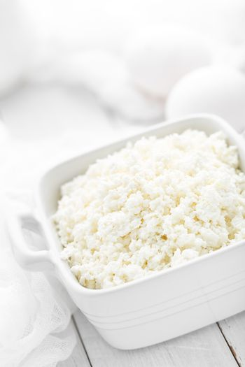 Cottage cheese on white wooden rustic background, dairy product