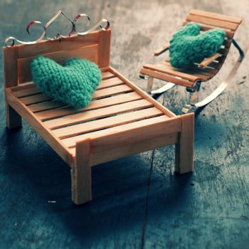 Two hearts be together, illustration for couple in love, take care and loving, green heart on handmade mini furniture as chair, swing, bed on wood background