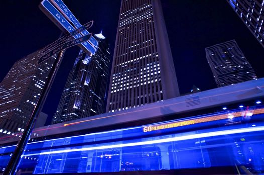 Metropolitan Bus in Motion. Night Bus Line. Chicago by Night. Long Exposure Wide Angle Bus in Motion with Skyscrapers in the Background. Horizontal Photography