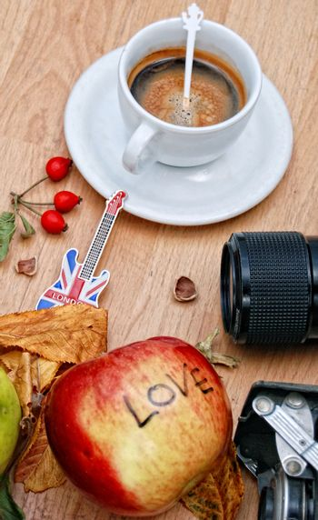 White cup of espresso, souvenir guitar from london, camera lens, rose hips and apple with text love