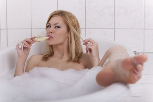 blonde woman in a bathtube with champagne