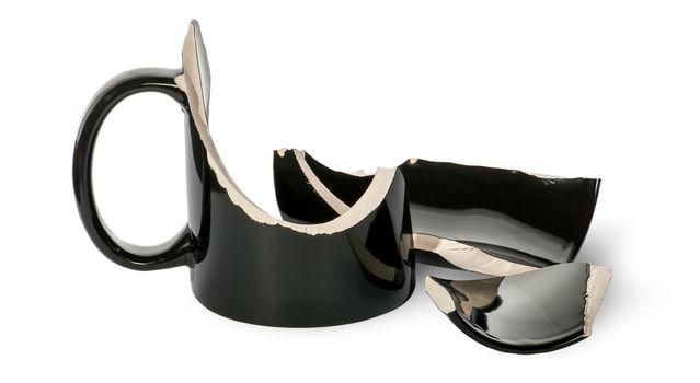 Broken black porcelain cup with fragments