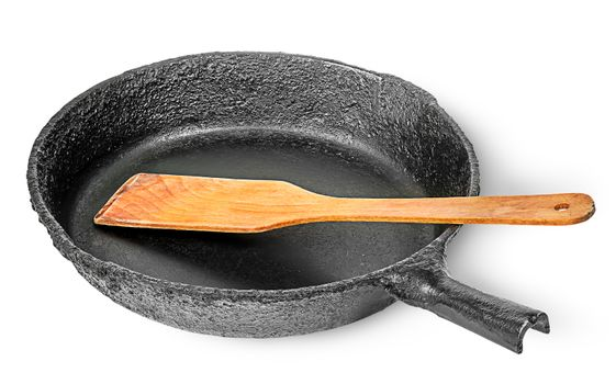 Old cast iron pan with wooden spatula