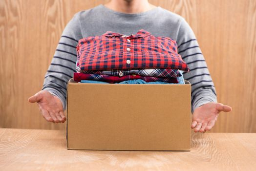 Donation box for poor with clothing in male hands