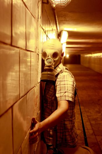 Man in a gas mask in the night tunnel