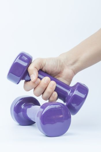 Woman hand holding dumbbell weight isolated on white background, stock photo