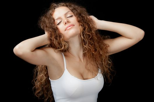 A beautiful young woman with gorgeous curly hair and white singlet stretching on black background.