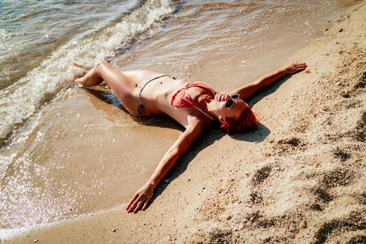 Beautiful young woman enjoying on the beach. She is lounging and sunbathing on the sandy coast in the sea.