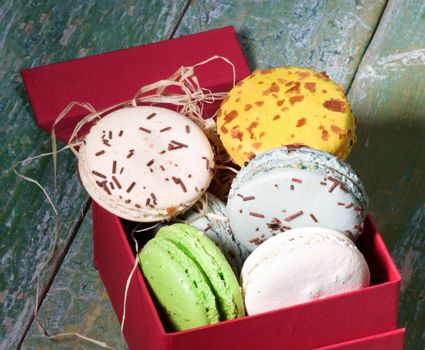 Assorted Traditional Colorful Macarons in Red Gift Box closeup on Green Cracked Wooden background