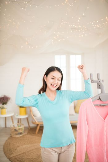 Happy young asian woman finish steaming clothes in room