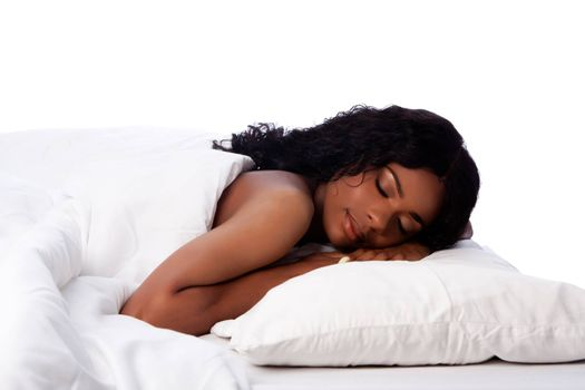 Attractive beautiful woman happily peacefully asleep on soft fluffy pillow and bed, on white.