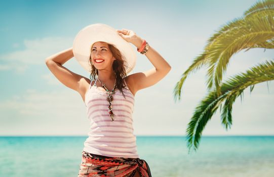 Beautiful young woman with summer hat enjoying on the beach. She is smiling and pensive looking away.