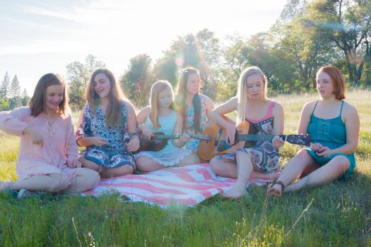 Girls Sitting Together in Grassy Field Singing and Playing Music