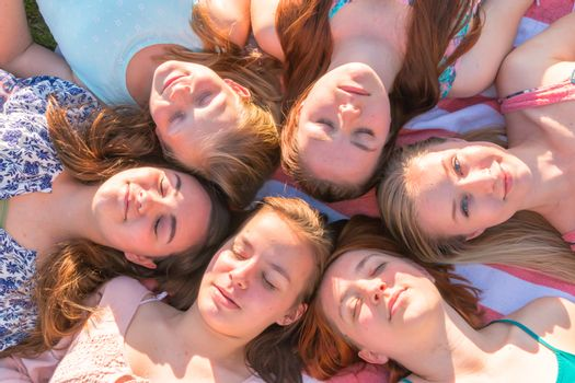 Girls Laying on the Ground Looking up, Some With Eyes Closed