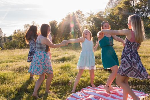 Girls Dancing in Grassy Field With Sunlight Overhead