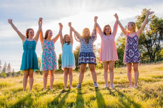 Girls Standing With Arms Raised and Sunlight Overhead