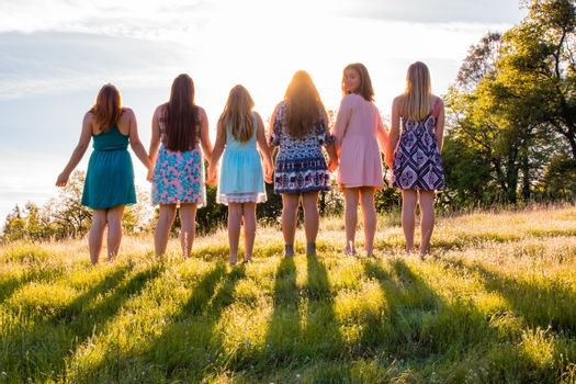 Girls Standing Together Facing the Bright Sunset