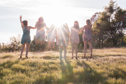 Girls Jumping Together Facing the Bright Sunset