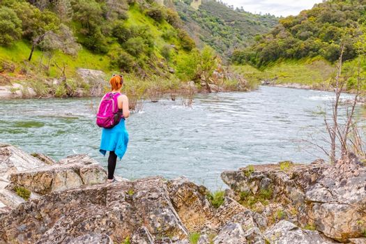 Girl Standing on Rocks Near Fast River
