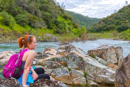 Girl Sitting on Rocks Near Fast River