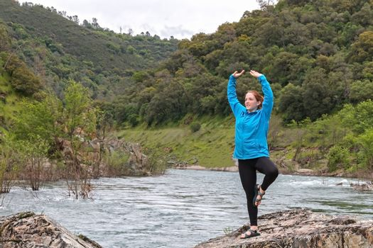 Girl Stretching on Rocks Near Fast River