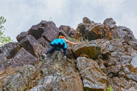 Girl Climbing up Rocks and Reaching