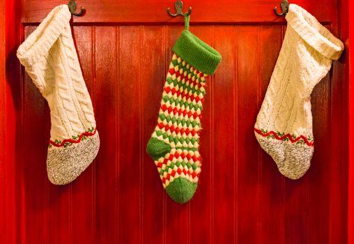 Three Stockings Hanging on Hooks