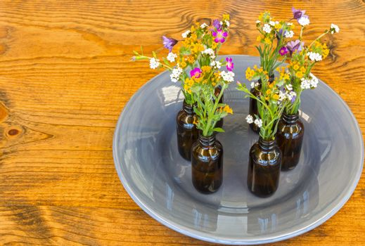 Gray Plate With Vases and Flowers on Table