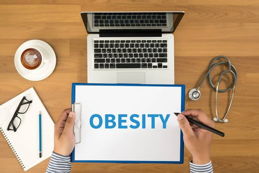 OBESITY Doctor writing medical records on a clipboard, medical equipment and desktop on background, top view, coffee