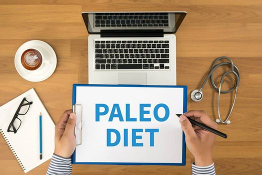 PALEO DIET Doctor writing medical records on a clipboard, medical equipment and desktop on background, top view, coffee