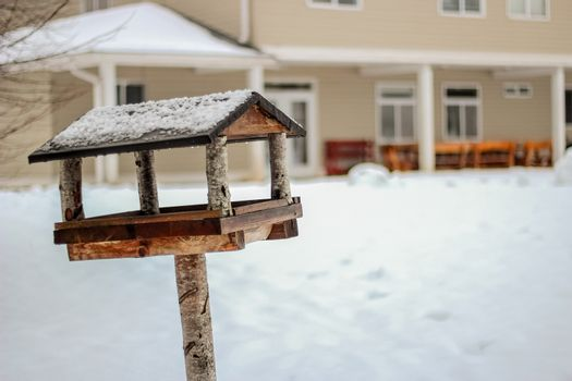 Wooden birdhouse in winter day close up