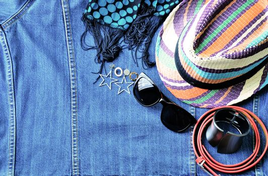 Top view of summer accessories for modern woman on her vacation stylish sunglasses Belt earring glasses Scarf, and striped beach  on denim jean background