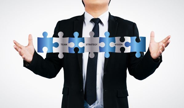 Business man showing  jigsaw puzzle  with team strategy vision wording. concept for business isolated on white background