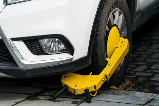 A car parks on forbidden parking lot, being wheel clamp lock