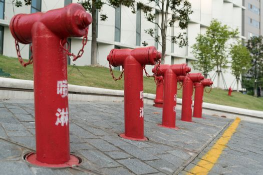 A group of red fire water hydrant beside the building