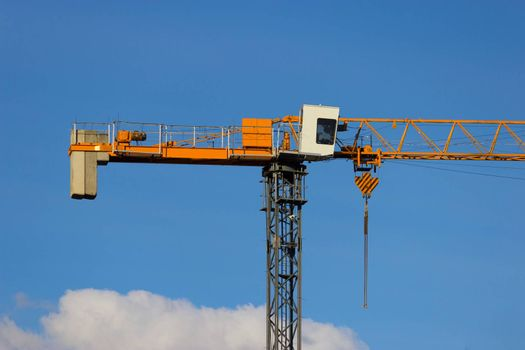 yellow construction crane on blue sky background