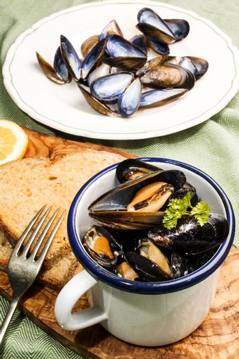 mussels with garlic and butter sauce in a blue and white enamel
