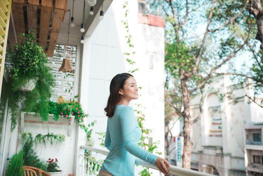 Beautiful asian girl enjoying the freshness on balcony
