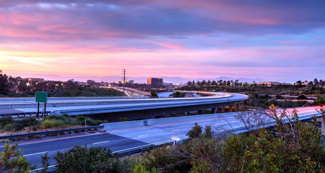 Car headlight trails at sunset traveling across a highway in New