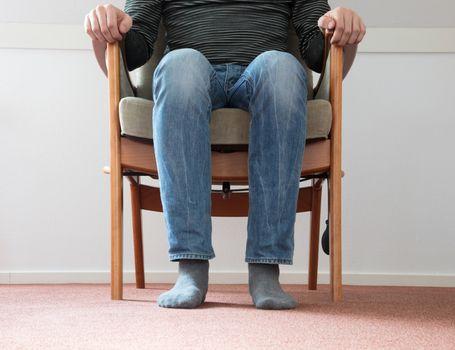 Man in armchair, slightly creepy