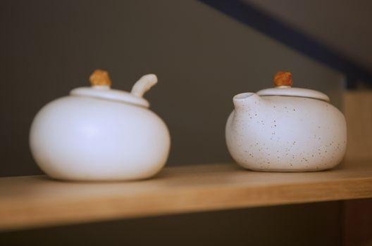 Two porcelain teapots on a kitchen shelf