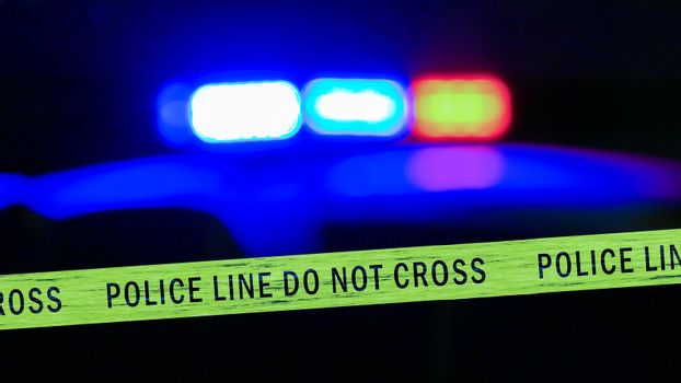 Defocused police car siren with boundary tape