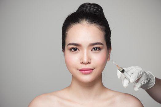 Beautiful asian woman gets beauty facial injections. Face aging