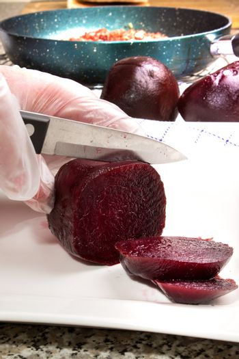 beetroot is cut from a female chef on a porcelain plate in slice