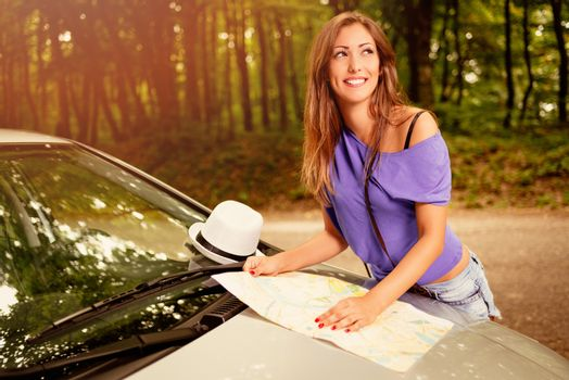Young beautiful woman standing by the car in the forest and looking a map.