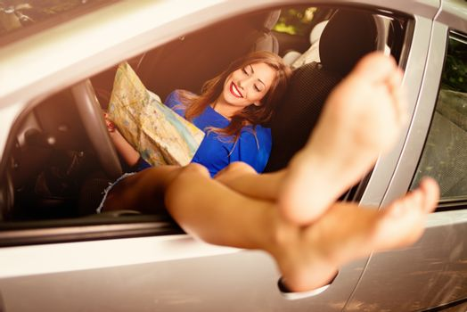 Beautiful smiling girl taking it easy in car, holding map and stretching her naked legs out the window of car. Selective focus.