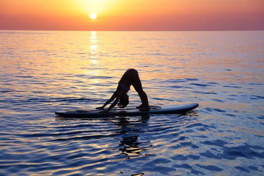Sportive female doing yoga exercise on the beach over beautiful sunset background, standing on the sup board on the water in Pose dog muzzle down, Adho Mukha Svanasana