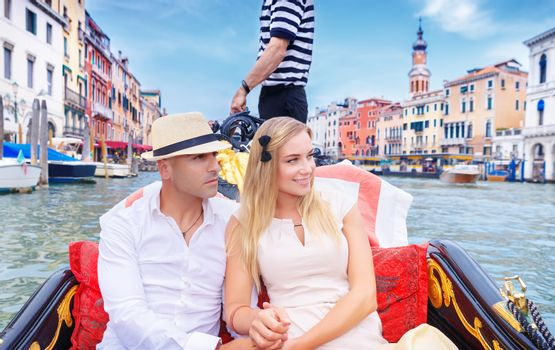Young happy couple riding on a gondola on Grand Canal in Venice, with pleasure spending honeymoon in Europe