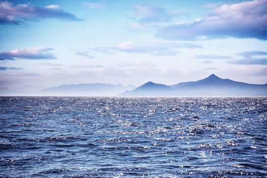 Beautiful sea landscape, amazing view on seascape in morning sunlight, silhouette of high mountains on the Greek islands, wonderful travel destination